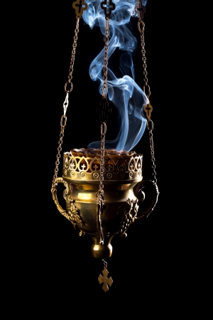 Hanging incense burner isolated on a black background