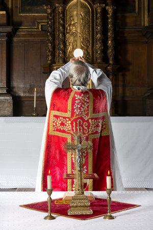 eucharistie: Prêtre pendant la consécration à l'ancienne, avec son dos au peuple, dans une église médiévale avec un intérieur du 17ème siècle