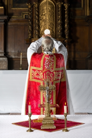 catholic mass: Priest during consecration the old way, with his back to the people, in a medieval church with 17th century interior