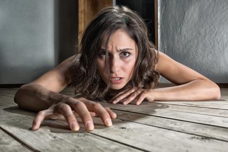 asustadotdo: Miedo mujer arrastrándose en el piso de una casa abandonada