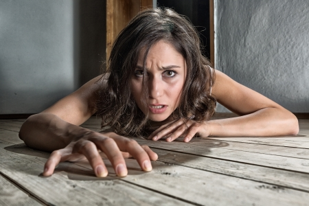 Scared woman crawling on the floor of a derelict house photo