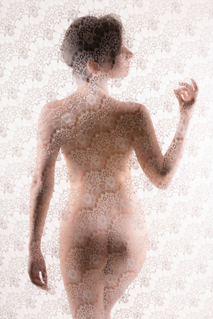 Hiding nude woman in silhouette behind a sheer white lace curtain photo