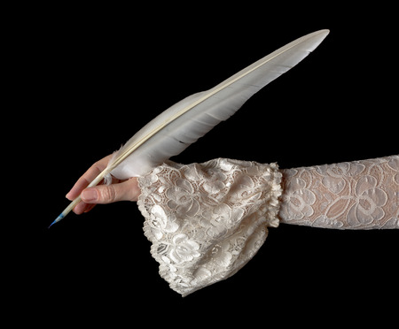 Female hand in antique sleeve writing with a quill feather photo