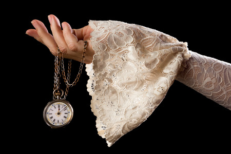 hand chain: Female hand in lace sleeve holding an antique pocket watch on a chain