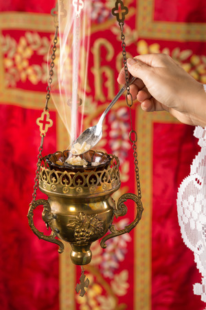 Frankincense: Hand adding incense chunks into a burning incense thurible