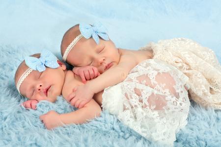 Dos bebés gemelos recién nacidos adorables dormido en una manta suave
