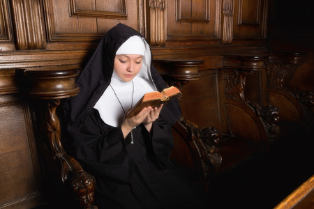 Novice nun reading a prayer book (shot in a 17th century church interior, all clothing and accessories authentic or antique) photo