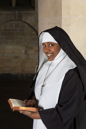 Smiling nun reading the bible in a medieval church photo