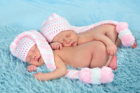 Two adorable newborn twin babies asleep on a soft blanket photo