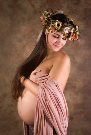 Fine Art image of a naked pregnant woman with chiffon fabrics and flower garland photo