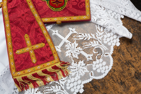 catholic mass: 19th century red damask chalice veil and maniple on a white lace catholic priest surplice