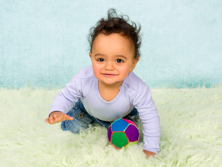 Cute African baby boy crawling in his little jeans photo