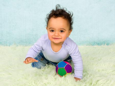 bebe gateando: Niño lindo bebé africano arrastra en sus pequeños pantalones vaqueros
