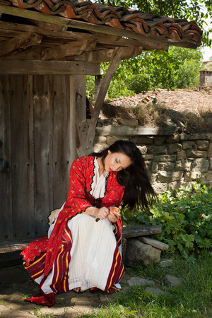 bulgarian ethnicity: Beautiful young woman in bulgarian national dress peeling an apple in the old village of Jeravna Stock Photo