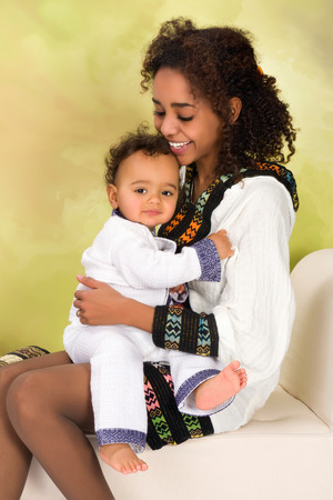 Ethiopian mother in national costume from her country playing with her baby photo