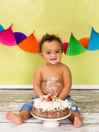 Adorable Afrikaanse baby tijdens een cake smash op zijn eerste verjaardag