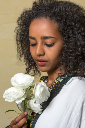 Beautiful Ethiopian young woman in traditional dress holding white roses photo