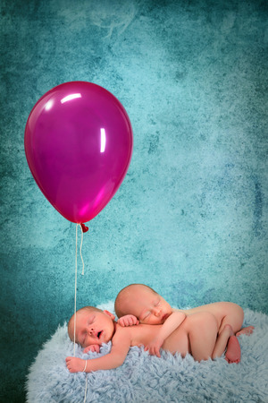 Adorable newborn twin babies asleep and holding a pink balloon photo