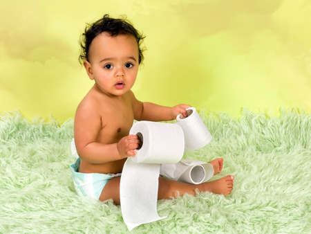 Adorable african baby boy playing with toilet paper photo