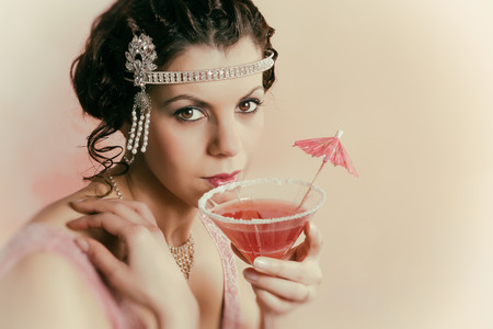 flapper: Beautiful young vintage 1920s woman with headband and flapper dress drinking a cocktail