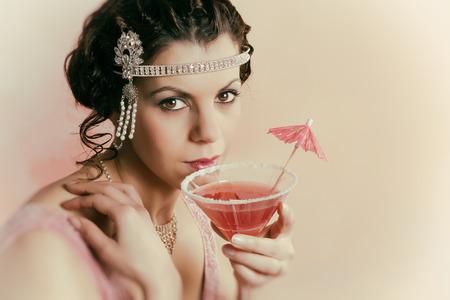 cintillos: Mujer hermosa joven con la vendimia 1920 diadema y vestido de trampa de beber un cóctel Foto de archivo