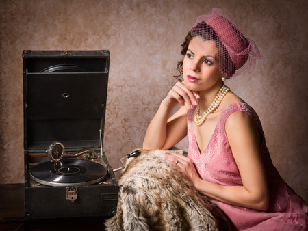 phonograph: Vintage 1920s style lady in pink listening to an antique record player
