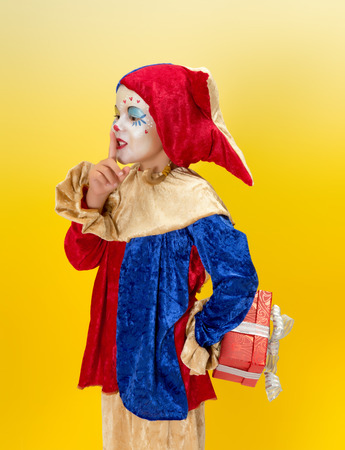 harlequin clown in disguise: Cute clown girl hiding a secret present behind her back