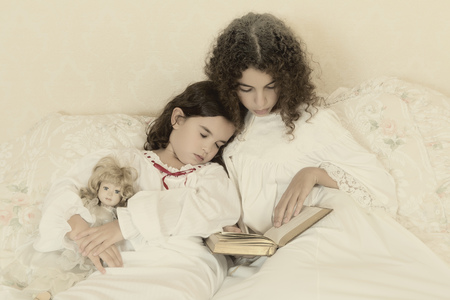 Vintage girl in bed reading a bedtime story to her little sister photo