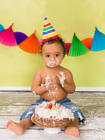 first birthday: Adorable african baby during a cake smash on his first birthday Stock Photo