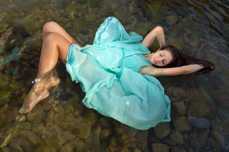 Beautiful woman in green dress floating in the shallow beach waters Stock Photo