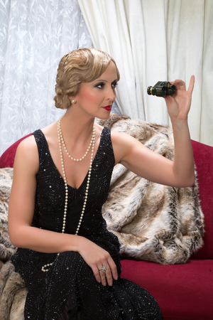Classy flapper dress lady holding a pair of opera glasses in a roaring twenties scene photo