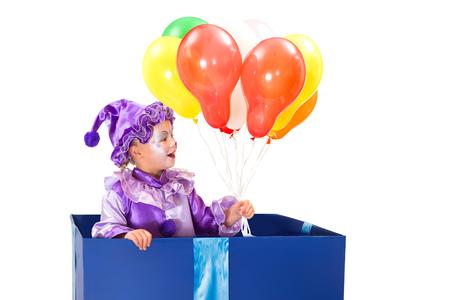 tonto: Pequeño payaso de cinco años en una caja de sorpresa que sostiene los globos