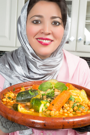 veiled: Smiling Moroccan immigrant woman in Europe presenting her tajine dish during Ramadan in her modern kitchen Stock Photo