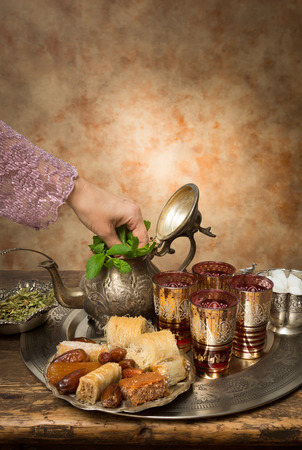 Female hand adding mint leaves on a Moroccan tea tray photo
