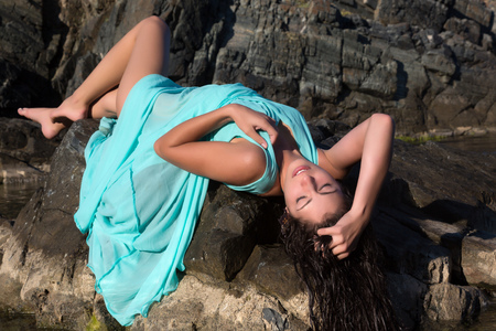 wet dress: Pretty young woman in a green chiffon dress on a beach rock Stock Photo