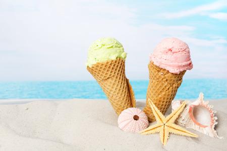 两个冰淇淋锥和贝壳在沙滩上在海滩