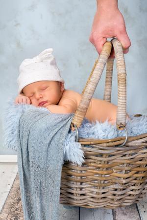 Adorable seven days old newborn baby boy in a wicker basket photo