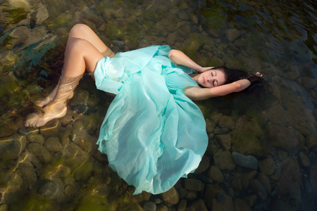 Beautiful woman in green dress floating in the shallow beach waters photo