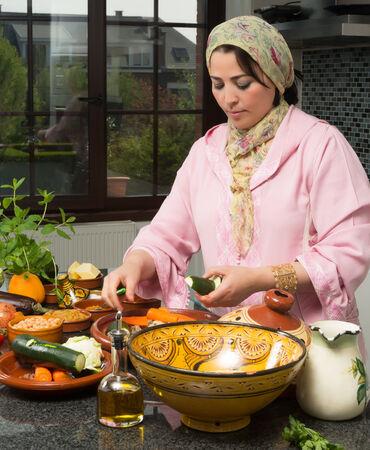 femmes muslim: Femme marocaine immigr�e dans la cuisine europ�enne moderne, pr�parer plat traditionnel tajine pour les nuits du Ramadan