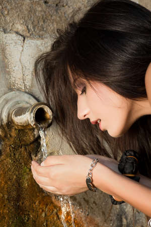 Young woman drinking fresh water from a well photo