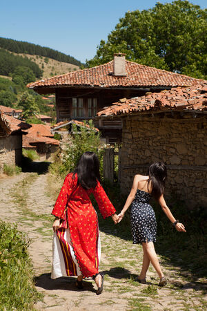 bulgarian ethnicity: Modern and traditional costume women walking in the village streets of Jeravna Bulgaria Stock Photo