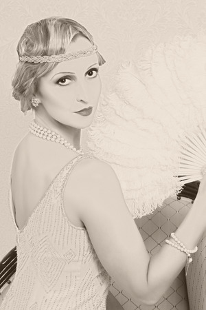 Old photo effect of a vintage twenties woman with feather fan photo