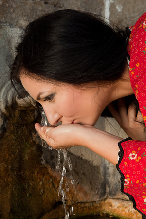bulgarian ethnicity: Young woman in bulgarian national dress drinking at an old well in the village of yeravna Stock Photo