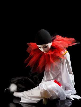 Sad Clown or Pierrot sitting on the black floor photo