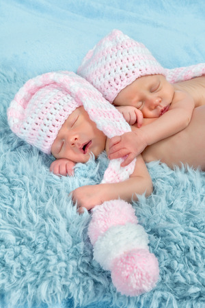 Two adorable newborn twin babies asleep on a soft blanket