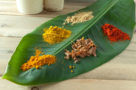 dried herbs: Nutmeg, curry, paprika, pepper and curcuma spices on a green banana leaf
