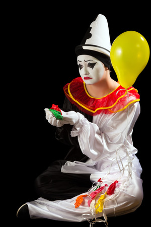 Crying pierrot clown holding exploded balloons in his hand photo