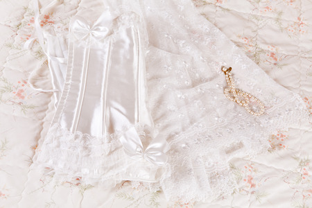 White lace wedding corset and bridal veil on a bed photo