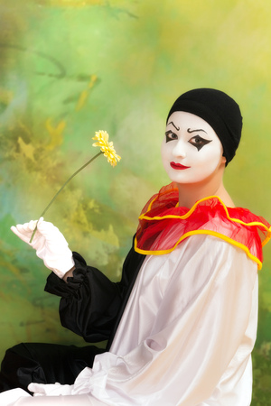 pierrot: Beautiful Pierrot clown holding a flower and smiling