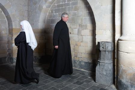 Nun passeren van een priester langs de muren van een middeleeuwse kerk
